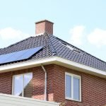 Solar Panels: A residential house with solar panels on the roof on a clear day.